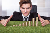 Businessman Looking At Stack Of Coins — Stock Photo