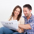 Happy Young Couple Sitting On Couch Reading Newspaper — Stock Photo