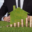 Businessman With Stack Of Coins And Eco Friendly House — Stock Photo