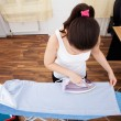 Foto Stock: Young Woman Ironing Clothes