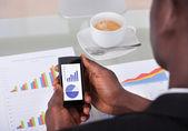 Businessman Analyzing Graph On Cellphone — Stock Photo