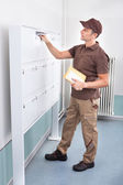 Postman Putting Letters In Mailbox — Stock Photo