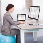 Woman Sitting On Pilates Ball Using Computer — Stock Photo