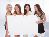 Four attractive women with blank sign — Stock Photo