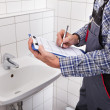Plumber Standing In Front Of Washbasin Writing On Clipboard — Stock Photo #39412399