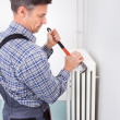 Stock Photo: Plumber Fixing Radiator