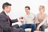 Salesman Giving Car Key To Couple — Stock Photo