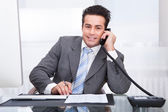 Young Businessman At Desk Talking On Telephone — Stock Photo