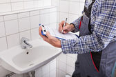 Plumber Standing In Front Of Washbasin Writing On Clipboard — Stock Photo