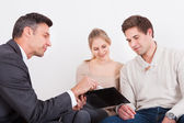Consultant Showing Clipboard To Couple — Stock Photo