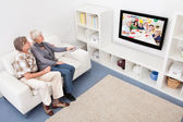 Senior Couple Changing Channel Of Television — Stock Photo