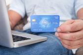 Persons hand visar kreditkort när du använder laptop — Stockfoto
