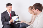 Advisor Showing Graph On Laptop To Couple — Stockfoto