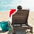 Woman with Santa hat relaxing on deck chair at beach resort — Stock Photo #42841825