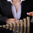 Businesswoman With Row Of Coins — Stock Photo #42842645