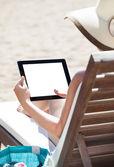 женщина с помощью цифрового планшета на шезлонг — Стоковое фото