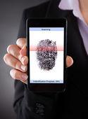 Businessperson With Cellphone Scanning A Fingerprint  — Stock Photo