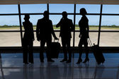 Businesspeople with luggage standing against airport window — Stock Photo
