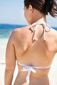 Young woman in bikini top standing at sunny beach — Stock Photo