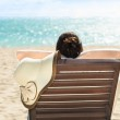 Woman with sunhat relaxing on deck chair at beach resort — Stock Photo