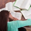 Female student sleeping with books at classroom desk — Stockfoto
