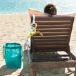 Woman with scuba mask relaxing on deck chair at beach resort — Stockfoto #43208431