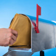 Man opening his mailbox to remove mail — Stock Photo