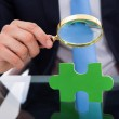 Businessman Scrutinizing Puzzle Piece With Magnifying Glass — Stock Photo