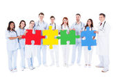 Medical team holding colorful puzzle pieces — Stok fotoğraf
