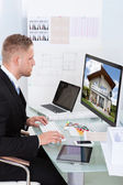 Businessman checking a property portfolio online — Stockfoto