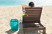 Woman with scuba mask relaxing on deck chair at beach resort — Stock Photo
