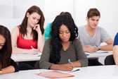College Students Writing At Desk — Stock Photo