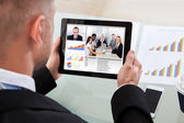Businessman on a video or conference call on his tablet — Stock Photo