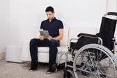 Handicapped Man Using Digital Tablet On Sofa — Stock Photo