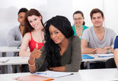 Confident Student Gesturing Thumbs Up In Classroom — Stock Photo