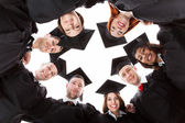Graduate students standing in circle leaning towards camera — Stock Photo
