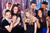 Friends Singing Into Microphones At Karaoke Party — Stock Photo