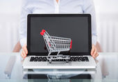 Businessperson With Shopping Cart And Laptop — Stock Photo