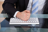Midsection of businessman pounding fist on keyboard — Stock Photo