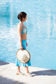 Young woman walking at poolside — Stock Photo