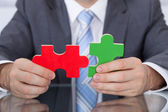 Businessman Fitting Two Puzzle Pieces Together — Stock Photo