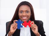 Säker affärskvinna med pusselbitar i office — Stockfoto