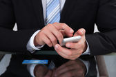 Businessman sending a text message or sms — Stock Photo
