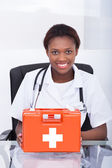 Doctor With First Aid Kit At Desk In Hospital — Stock Photo