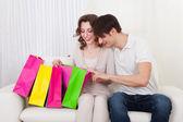 Gelukkige paar zittend op de bank met shopping tassen — Stockfoto