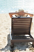 Woman relaxing on deck chair at tropical beach — Stock Photo