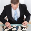 Businessman solving a jigsaw puzzle at his desk — Stock Photo