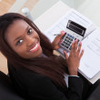 Confident Businesswoman Calculating Tax At Desk — Stock Photo #43675347