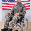Patriotic Soldier Sitting On Wheel Chair Against American Flag — Stock Photo #43675983