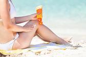 Mujer en bikini aplicar protector solar a orillas del mar — Foto de Stock